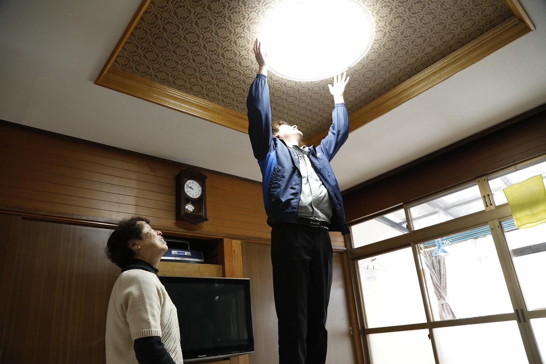 電球を取り換えるスタッフ